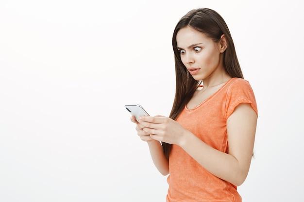 Шокированная привлекательная девушка, вытаращивая глаза на экран, с тревогой смотрит на дисплей мобильного телефона