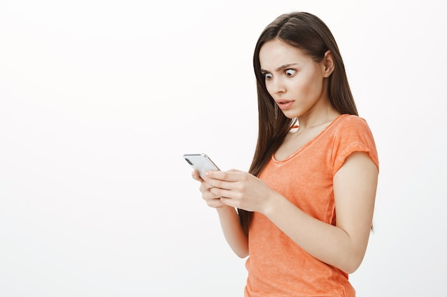 Shocked attractive girl popping eyes at screen, stare mobile phone display with anxious look