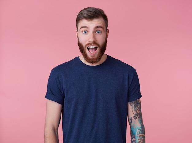 Шокированный привлекательный рыжебородый молодой парень с голубыми глазами, одетый в синюю футболку, смотрит в камеру с широко открытым ртом и удивленно кричит на розовом фоне.