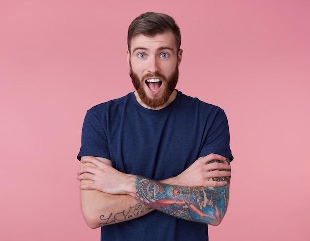 Шокированный привлекательный рыжебородый молодой парень с голубыми глазами, в синей футболке, со скрещенными руками, смотрит в камеру с широко открытым ртом и удивленно кричит на розовом фоне.