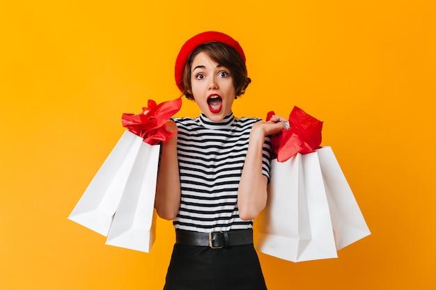 Шокированная привлекательная женщина позирует после покупок