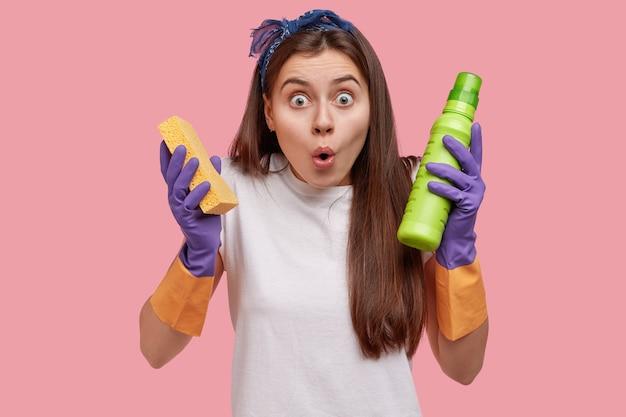Giovane femmina attraente scioccata dal servizio di pulizia, tiene la spugna e il detersivo, mantiene la mascella aperta