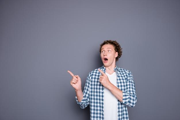 2本の指を脇に向けるカジュアルな市松模様のシャツを着たショックを受けた魅力的な若い男