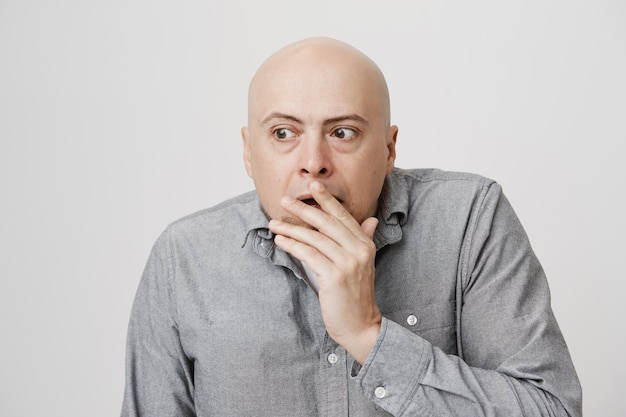 Шокированный лысый мужчина средних лет подслушивает