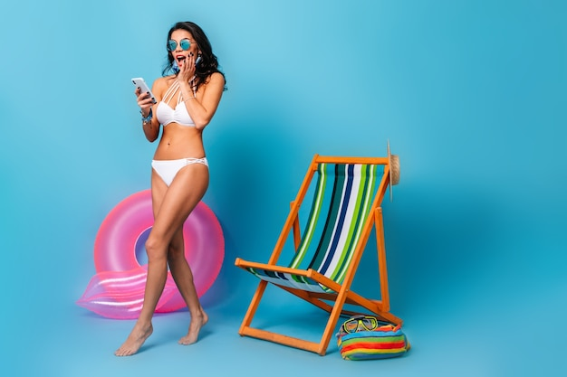Shocked barefooted woman in bikini holding smartphone