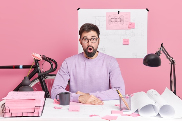 Shocked bearded adult male office worker looks with excitement, sits at desktop with blueprints and papers prepares engineering project surprised to have deadline. designing concept