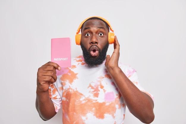 Шокированный бородатый взрослый мужчина слушает музыку перед рейсом. паспорт готов к поездке, узнает удивительные новости, одетый в повседневную футболку, изолированную над белой стеной, получил отказ в получении визы