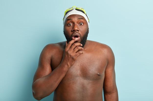 Allenatore di nuoto afroamericano barbuto scioccato con il fiato sospeso, posa al coperto con il corpo nudo, ha una pelle sana e scura, indossa cappello da nuoto e occhiali protettivi, dà lezioni di gattonare in acqua