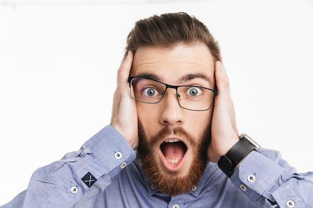 Шокированный бородатый элегантный мужчина в очках закрывает уши и смотрит с открытым ртом