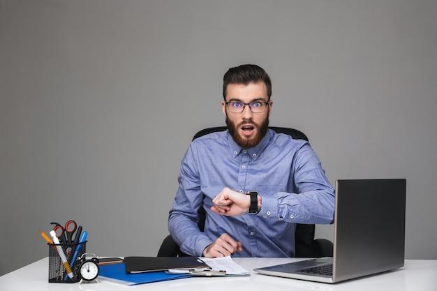 Шокированный бородатый элегантный мужчина в очках смотрит прямо, сидя за столом в офисе