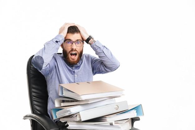 Шокированный бородатый элегантный мужчина в очках сидит на кресле с папками, держа голову и глядя
