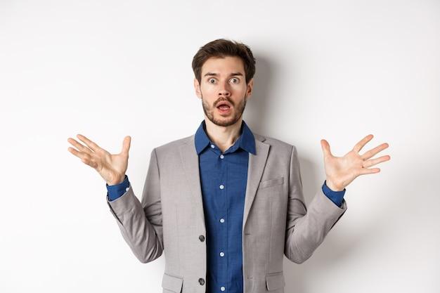 재킷에 충격을받은 수염 난 남자가 손을 옆으로 벌리고 헐떡이며 걱정스러워하며 양복을 입고 분홍색 배경에 서 있습니다.