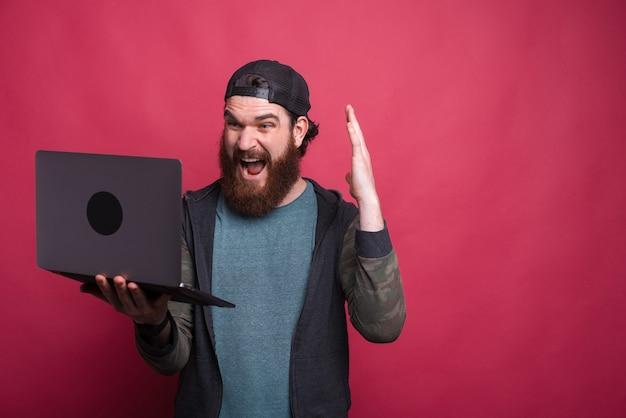 ショックを受けたひげを生やした男はピンクの背景に彼のラップトップを見ています。