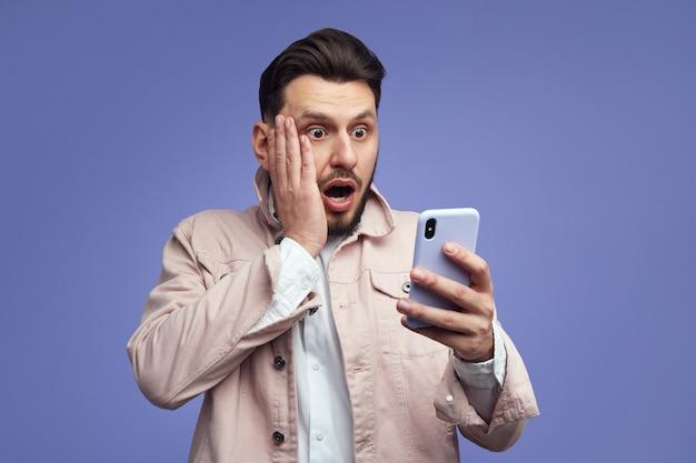 Шокированный бородатый мужчина с широко открытым ртом держит современный мобильный телефон