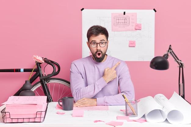 Scioccato uomo barbuto impiegato punti sul muro rosa dimostra schizzi pose sul desktop scrive informazioni su adesivi ha lavoro a distanza si siede nello spazio di coworking