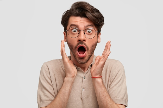 Shocked bearded man recieves unexpected news from friend, clasps hands near face, opens mouth widely, expresses surprisement, isolated on white wall