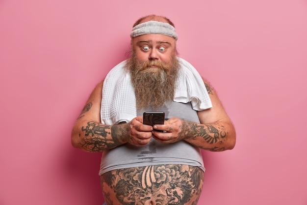 Uomo barbuto scioccato in abbigliamento sportivo, si prende una pausa dopo gli esercizi fisici a casa, tiene in mano lo smartphone, brucia calorie e grassi, scarica l'applicazione, posa contro un muro roseo. ragazzo grasso e spesso con gadget