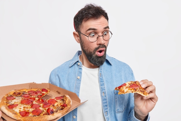 Shocked bearded man stares at slice of pizza eats fast food wears round spectacles and casual shirt has good appetite being very hungry poses indoor against white wall. service delivery