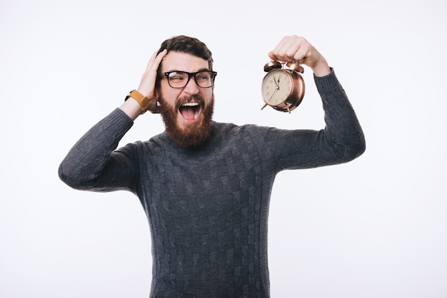 Shocked bearded man in sweater looking at alarm watch