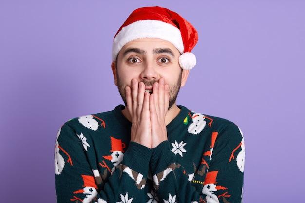 サンタの帽子とプルオーバーを着て、雪だるまが顔に触れて驚いた表情のショックを受けたひげを生やした男。ハンサムな若い男はカメラを見て、口を覆っています。クリスマスと新年のコンセプトです。