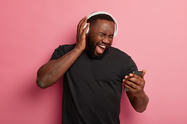 Shocked bearded man with dark skin excited from winning big discounts