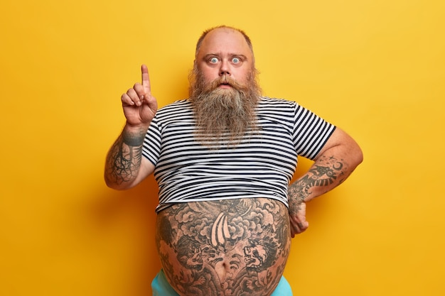 Shocked bearded man with fat abdomen points index finger above, shows something stunning, canot believe his eyes, stunned by big sale, has tattoed body, recommends or suggests good offer, discount