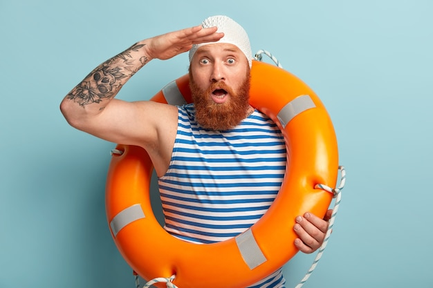 Потрясенный бородатый рыжеволосый мужчина удивительно смотрит вдаль, держит ладонь у лба, широко раскрытый рот