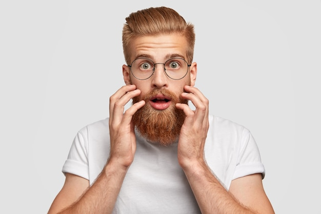 Shocked bearded red haired man looks with stunned expression directly at camera, keeps hands near cheeks