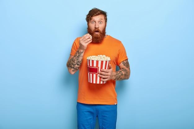 Uomo rosso barbuto scioccato in posa con popcorn