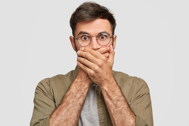 Shocked bearded young guy covers mouth with hands, has frightened expression, stares with eyes popped out, being speechless and mute, isolated over white wall. people, reaction concept