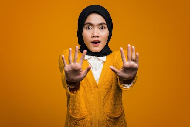 Shocked beautiful asian woman doing stop gesture