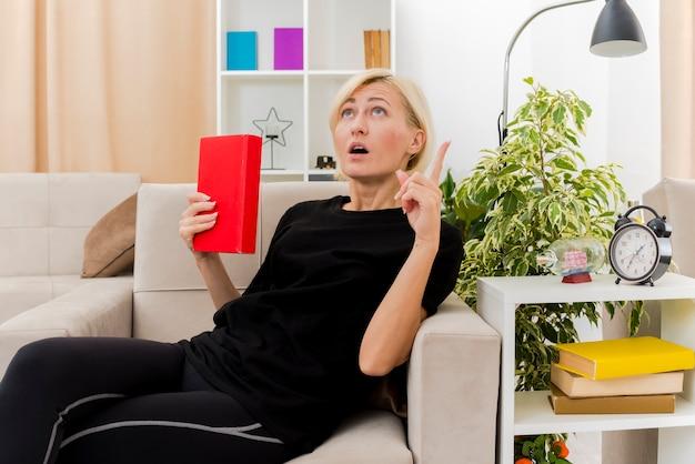 Scioccata bella bionda donna russa sdraiata sulla poltrona che tiene il libro alla ricerca e rivolto verso l'alto all'interno del soggiorno