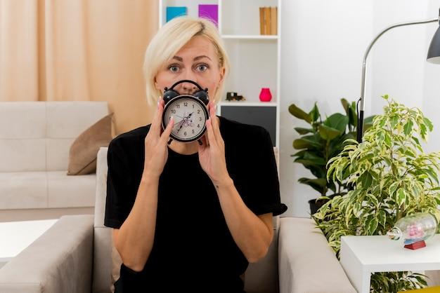 La bella donna russa bionda scioccata si siede sulla poltrona che tiene e che esamina la sveglia