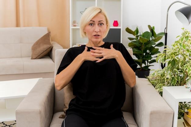 Bella donna russa bionda scioccata si siede sulla poltrona mettendo le mani sul petto all'interno del soggiorno