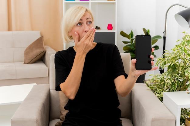 충격을받은 아름다운 금발의 러시아 여자는 거실 내부에 전화를 들고 입에 손을 넣어 안락 의자에 앉아