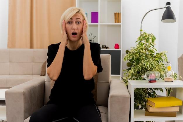 ショックを受けた美しい金髪のロシアの女性は、リビングルームの中で顔に手を置いて肘掛け椅子に座っています