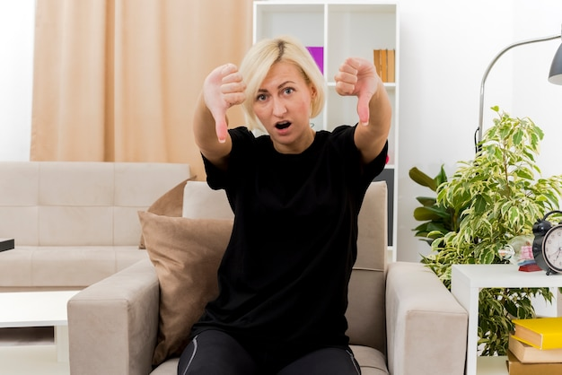 충격을받은 아름다운 금발의 러시아 여자가 두 손으로 안락 의자 엄지 손가락에 앉아있다.
