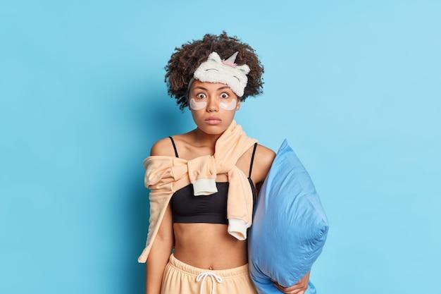 ショックを受けた美しい巻き毛の若いアフロアメリカ人女性は、パジャマに身を包んだバグのある目を凝視し、青いスタジオの壁に隔離された柔らかい枕を保持している素晴らしいニュースを見つけます
