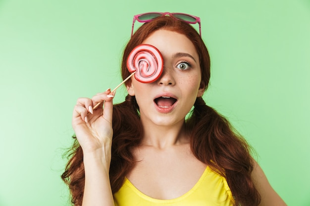 Shocked beautiful excited young redhead girl posing isolated over green wall background with candy.