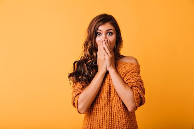 Bella ragazza scioccata in abbigliamento arancione che copre il viso con le mani. ritratto dell'interno dell'affascinante signora bianca che posa sul giallo con stupore.