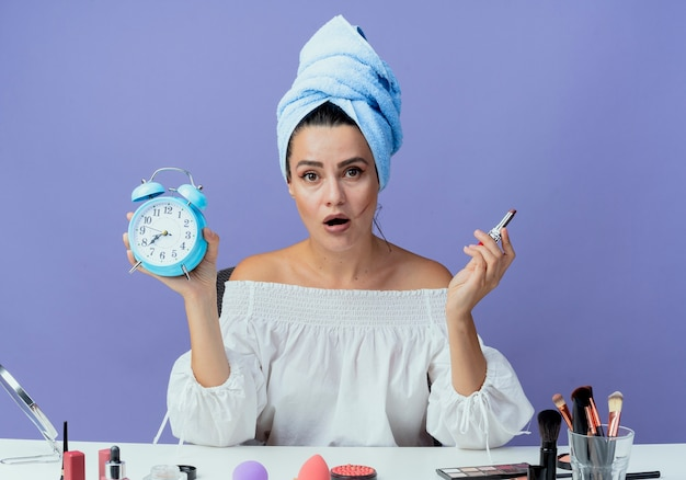 Shocked beautiful girl wrapped hair towel sits at table with makeup tools holding lipstick and alarm clock looking isolated on purple wall