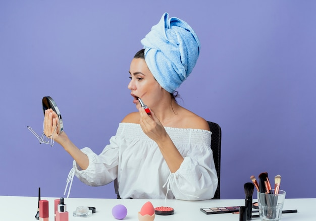 Shocked beautiful girl wrapped hair towel sits at table with makeup tools holding lipstick looking at mirror isolated on purple wall