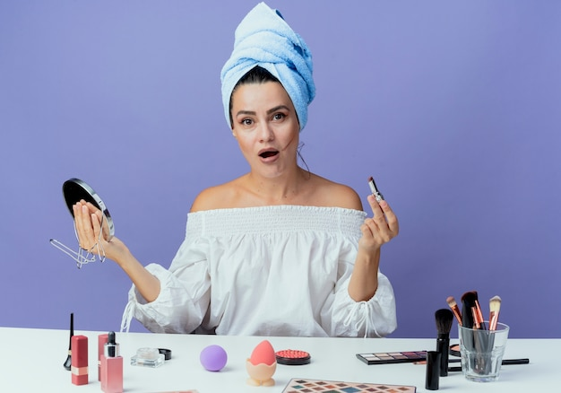 Shocked beautiful girl wrapped hair towel sits at table with makeup tools holding lipstick and mirror looking isolated on purple wall