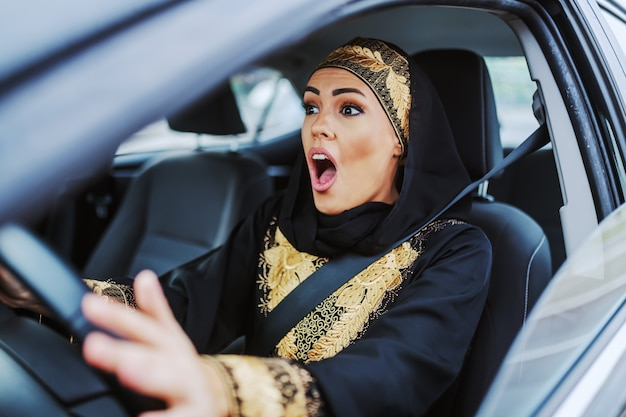 彼女の車に座っている伝統的な服装でショックを受けた美しいイスラム教徒の女性とちょうど自動車事故がありました。