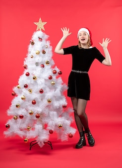 Bella donna scioccata in vestito nero e cappello di babbo natale in piedi vicino all'albero di natale bianco sul rosso