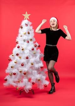 Bella donna scioccata in vestito nero e cappello di babbo natale in piedi vicino all'albero di natale bianco
