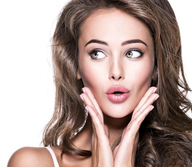 Bella donna scioccata con la bocca aperta che osserva. ritratto isolato del primo piano su fondo bianco