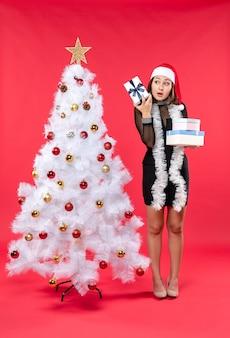 Bella donna scioccata con cappello di babbo natale e in piedi vicino all'albero di natale decorato