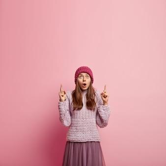 Шокированная красивая женщина с широко открытым ртом, одетая в шляпу, вязаный джемпер и длинную юбку, указывает вверху на пустое место для вашей рекламы. люди, удивление, реклама
