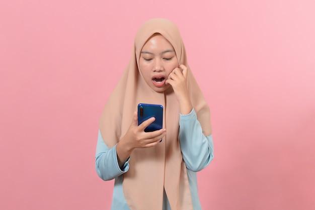 ピンクの背景で隔離のスマートフォンを見てショックを受けた美しい若いイスラム教徒の女性